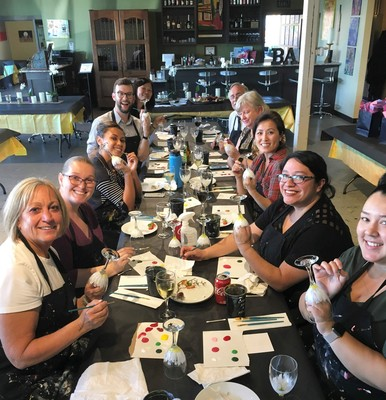 A group enjoying a wine glass paint event.